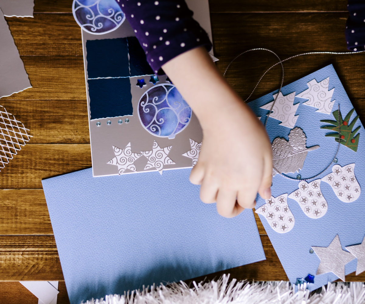 Little girl making Christmas cards on wooden background